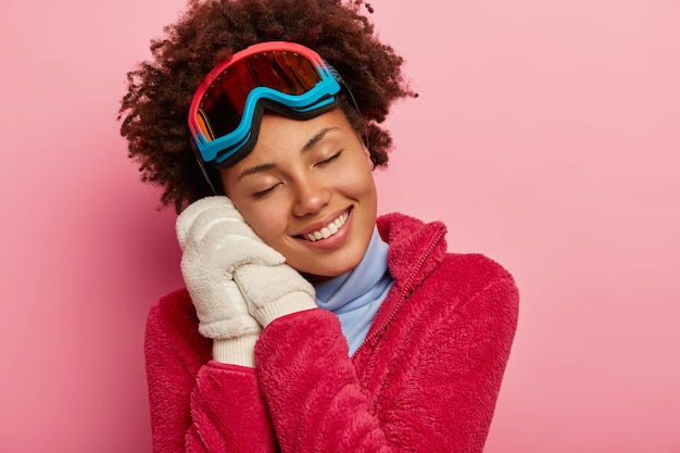 Conceito de diversão, recreação e estilo de vida de inverno. mulher de pele escura usa óculos de snowboard apoiados em ambas as mãos e luvas brancas, lembra-se do momento agradável das férias