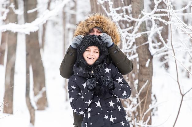 Conceito de diversão, temporada e lazer - casal apaixonado joga madeira de inverno na neve.