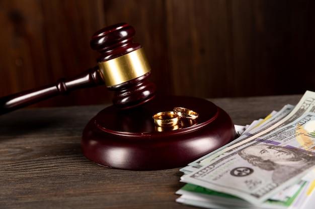 Conceito de divórcio. anéis de ouro na mesa com dinheiro e martelo de madeira.