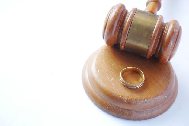 Conceito de divórcio com martelo e anéis de casamento na mesa