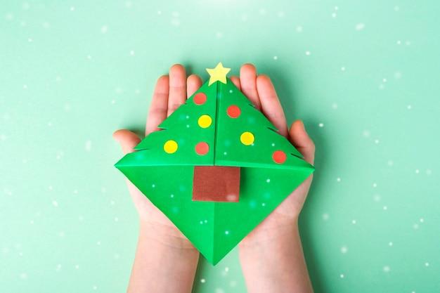 Conceito de diy e criatividade infantil, origami. mão de criança segurando o marcador como árvore de natal.