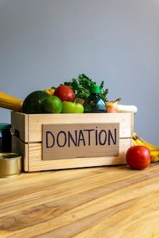 Conceito de doação de alimentos. caixa de doação com legumes, frutas e outros alimentos para doação