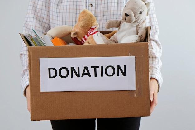 Conceito de doação. homem segurando a caixa cheia de livros e brinquedos. doe para crianças por favor
