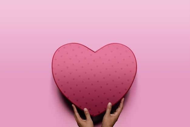 Conceito de doação. mãos do doador dando uma caixa de coração vermelha a um destinatário
