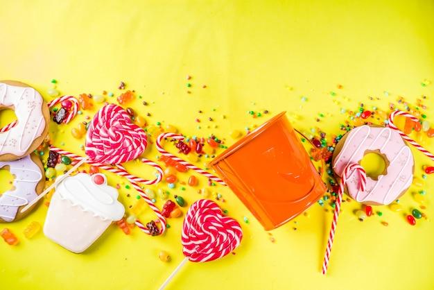 Conceito de doces de halloween, balde em forma de uma abóbora festiva, cheia de doces e balas
