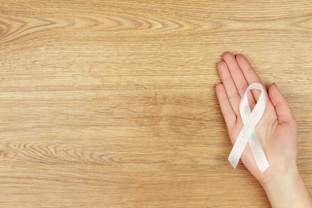 Conceito de doença oncológica. a mão de uma mulher com uma fita branca como um símbolo do câncer de pulmão isolado no fundo de madeira.