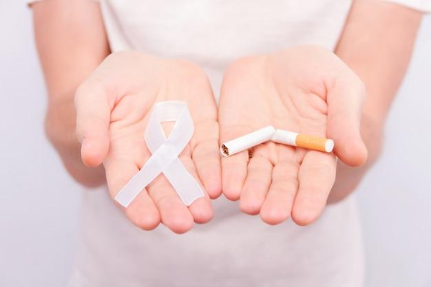 Conceito de doença oncológica. cara de camiseta branca segurando a fita branca como símbolo de câncer de pulmão em uma mão e cigarro quebrado na outra.