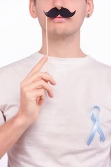 Conceito de doença oncológica. homem com bigode decorado, vestindo camiseta branca com a fita azul clara como um símbolo de câncer de próstata, preso ao lado do coração.
