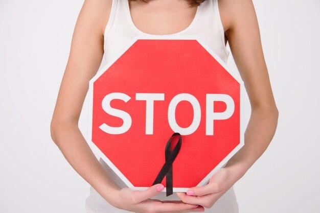 Conceito de doença oncológica. menina / fêmea / mulher / adulto que veste a parte superior branca que guarda o sinal vermelho da parada com fita preta como símbolo do melanoma.