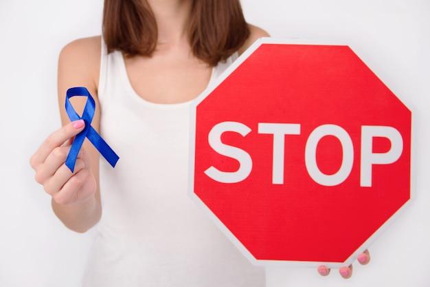 Conceito de doença oncológica. menina / mulher / fêmea / adulto que veste a parte superior branca que guarda o sinal vermelho da parada com fita azul escuro como símbolo do câncer de bacia.