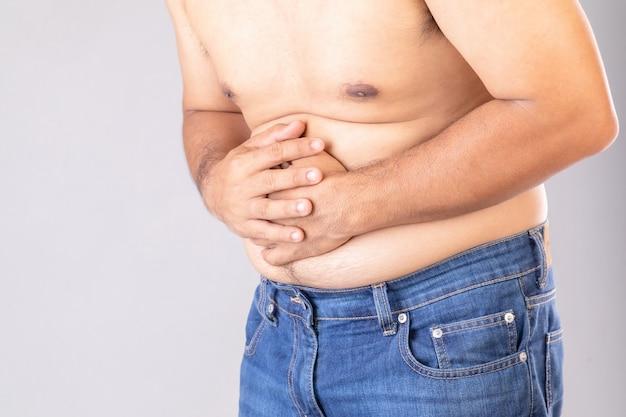 Conceito de dor de estômago ou dor na barriga: homem gordo usando a mão e pressionando o estômago