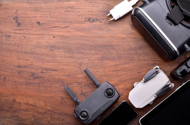 Conceito de drone hobby racing. equipamento de drone, controle remoto, receptor de vídeo, carregador, celular e quadcopter. vista superior do close up copie o espaço para o texto.