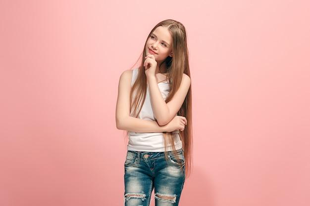 Conceito de dúvida. menina adolescente duvidosa e pensativa, lembrando de algo. emoções humanas, conceito de expressão facial. adolescente posando na parede rosa