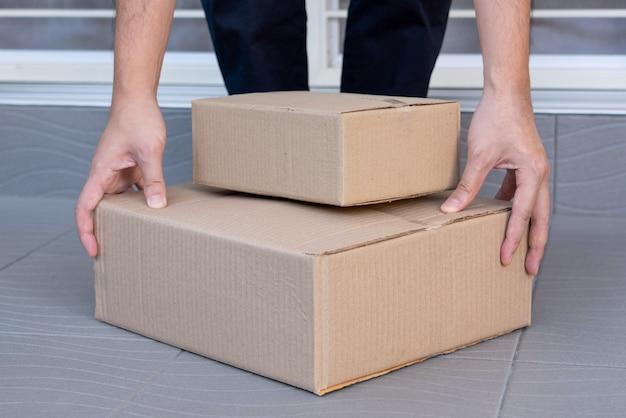 Conceito de e-commerce um homem saindo de casa e levantando as caixas para enviá-las aos seus clientes via tracking expresso.