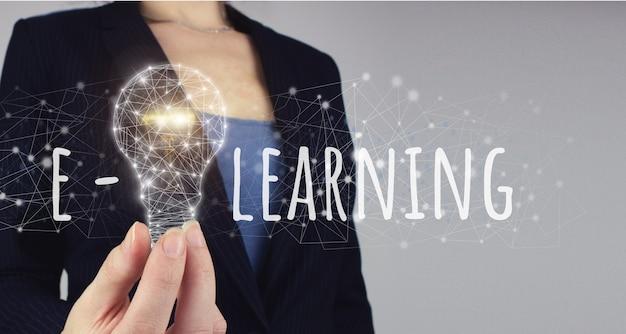 Conceito de e-learning. conceito de cursos on-line de educação de e-learning. mão segure a lâmpada digital. ideia de aprendizagem online.
