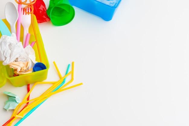 Conceito de ecologia de perigo de resíduos plásticos com lixo e canudos de uso único coloridos, copos de talheres, garrafas em fundo branco