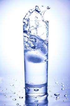Conceito de ecologia. respingo do gelo jogado em um copo de água limpa