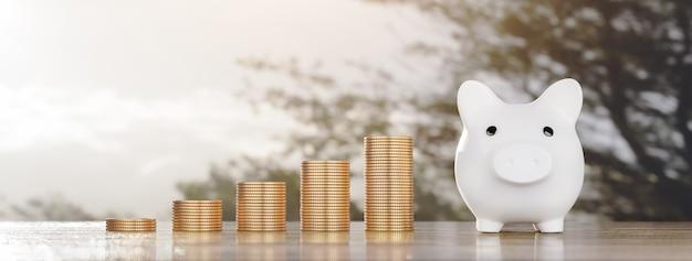Conceito de economia de dinheiro cofrinho com pilha de moedas de dinheiro tamanho do banner de crescimento de renda positiva