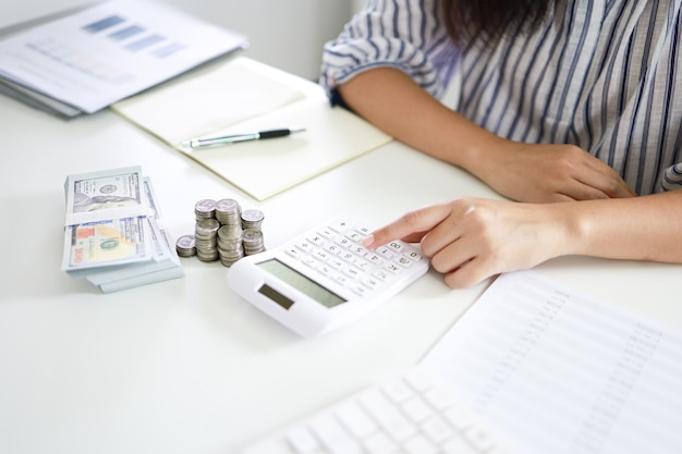 Conceito de economia de dinheiro mulher financeira mão pilha moedas dinheiro notas