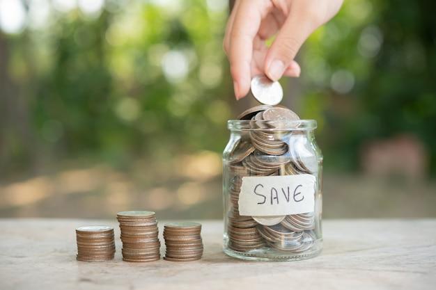 Conceito de economia de dinheiro predefinido por masculino mão colocando dinheiro moeda pilha de negócios em crescimento. organize as moedas em pilhas com as mãos, contente com o dinheiro.