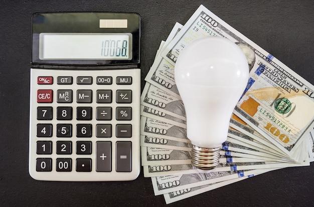 Conceito de economia de energia lâmpada com calculadora e dólares no preto