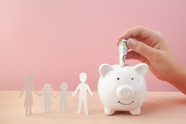 Conceito de economia familiar com cofrinho e corte de papel familiar