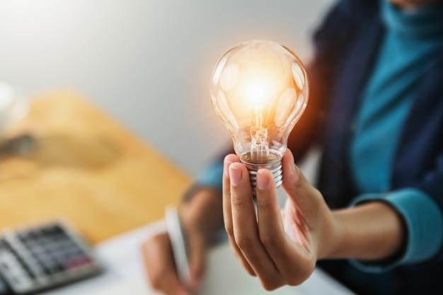 Conceito de economizar energia. empresária, segurando a lâmpada no escritório