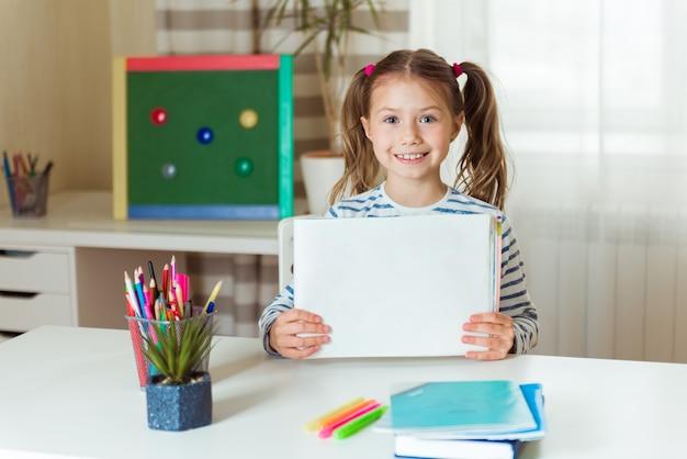 Conceito de educação a distância. confinamento do covid. menina caucasiana aprende a desenhar online durante o auto-isolamento