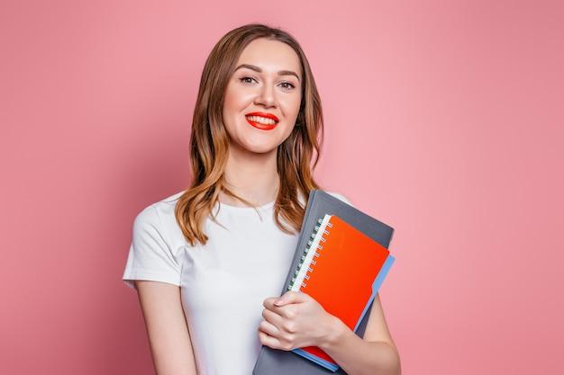 Conceito de educação. aluna feliz caucasiana sorrindo olha para a câmera e segurando cadernos, pastas de livros nas mãos isoladas no fundo rosa do estúdio