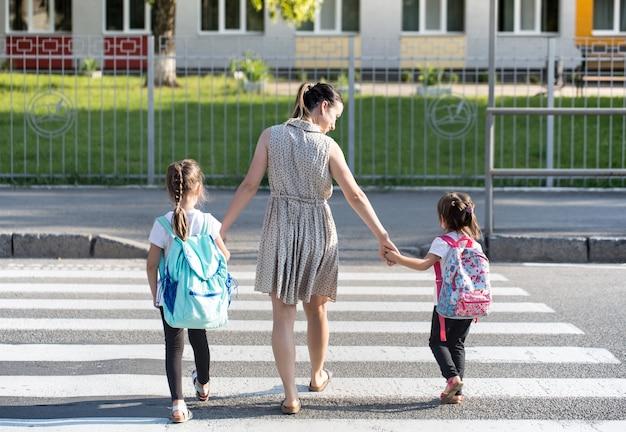Conceito de educação de volta à escola com garotas, alunos do ensino fundamental, carregando mochilas para ir para a aula