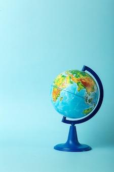 Conceito de educação e globalismo. globo em um livro aberto sobre uma mesa em uma aula universitária, sobre um fundo azul