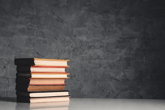 Conceito de educação e leitura - grupo de livros coloridos na mesa branca sobre o fundo cinza