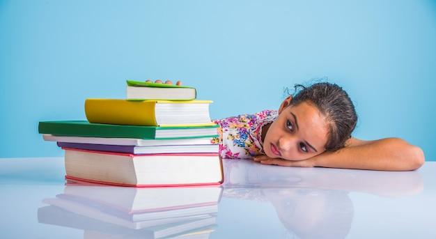 Conceito de educação em casa - linda menina indiana ou asiática estudando em casa com pilha de livros, globo educacional etc. foco seletivo