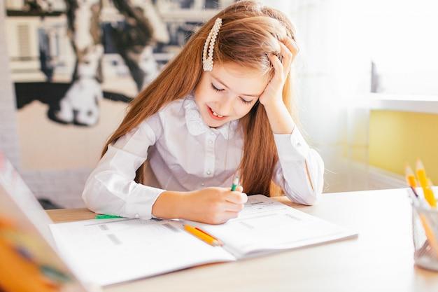 Conceito de educação em casa - menina bonitinha com cabelos longos, estudando ou concluindo o trabalho em casa sobre uma mesa com pilha de livros e pasta de trabalho