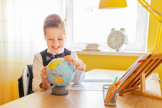 Conceito de educação em casa - menino bonitinho estudando ou concluindo o trabalho em casa na mesa de estudo com um globo e uma pasta de trabalho