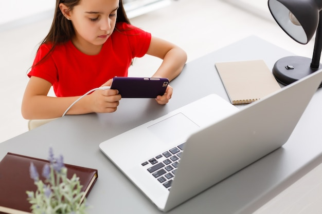 Conceito de educação, escola, tecnologia e internet - menina estudante com smartphone em casa