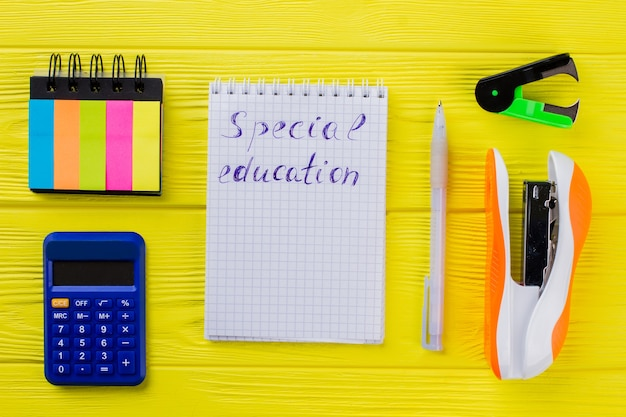 Conceito de educação especial plana leigos. bloco de notas com caneta e outros acessórios de papelaria na mesa de madeira amarela.