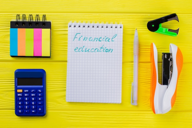 Conceito de educação financeira plana leigos. bloco de notas com caneta e outros artigos de papelaria na mesa de madeira amarela.