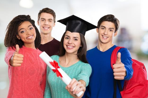 Conceito de educação - garota feliz no chapéu de formatura com diploma e alunos