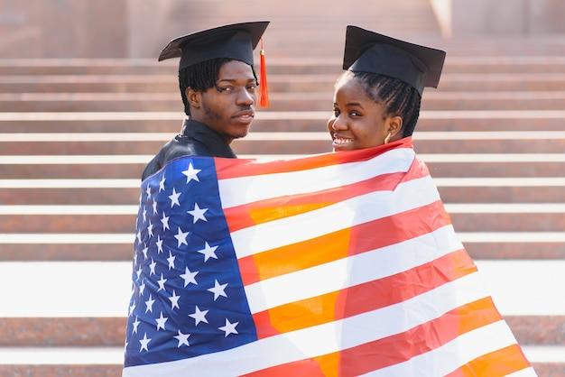 Conceito de educação, graduação e pessoas - estudantes internacionais felizes em chapas de argamassa e vestidos de solteiro com a bandeira americana