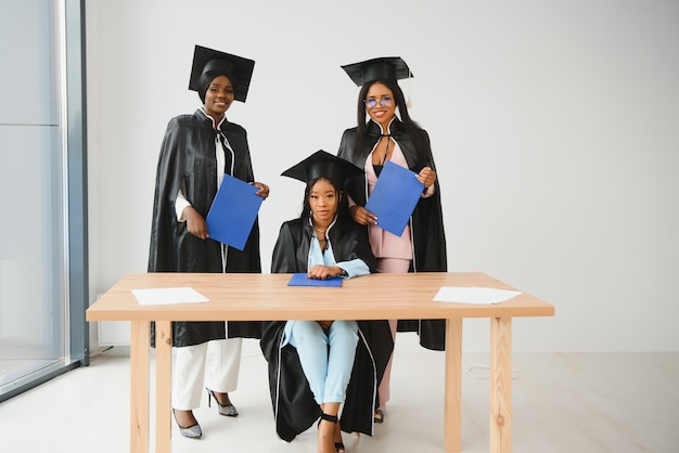 Conceito de educação, graduação e pessoas - grupo de felizes estudantes internacionais de pós-graduação em placas de argamassa e vestidos de solteiro com diplomas