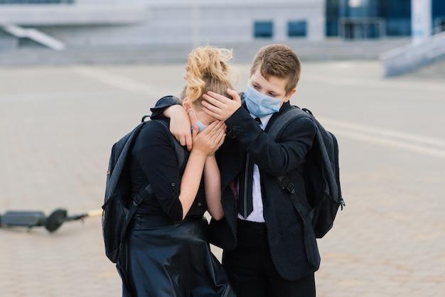 Conceito de educação, infância e pessoas. alunos chateados com mochilas e scooters ao ar livre com máscara protetora