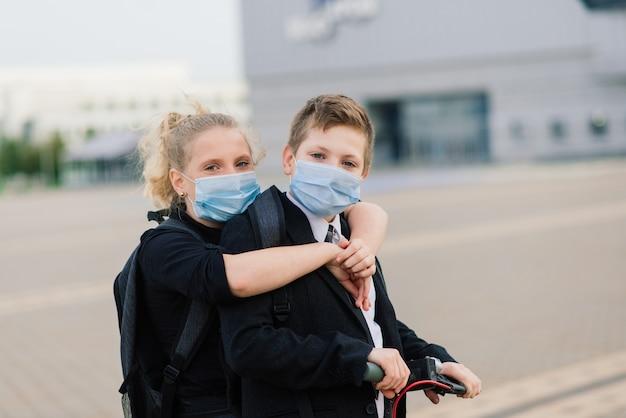 Conceito de educação, infância e pessoas. alunos felizes com mochilas e patinetes ao ar livre com máscara protetora