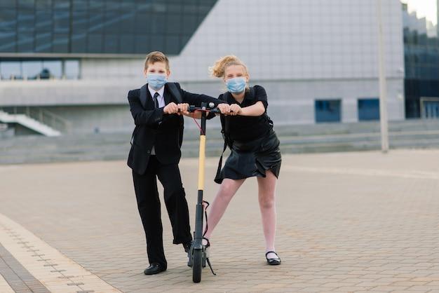 Conceito de educação, infância e pessoas. crianças em idade escolar felizes com mochilas e scooters ao ar livre com máscara protetora