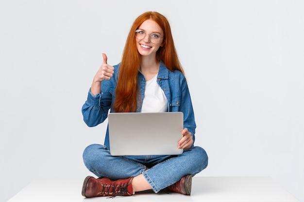 Conceito de educação, internet e pessoas. nômade digital ruiva feminina, freelance garota de óculos, projeto concluído antes do prazo, sentada no chão com as pernas cruzadas e laptop, aparecer o polegar