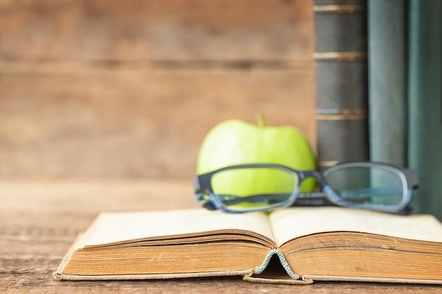 Conceito de educação livros óculos e maçã no fundo de madeira e lugar para texto