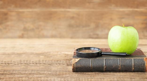 Conceito de educação lupa de livro antigo e maçã verde em um fundo de madeira e lugar para texto