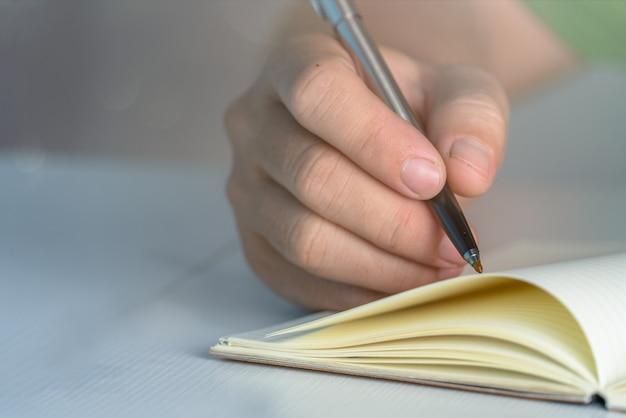 Conceito de educação. mão homem escrever caderno na mesa mesa branca