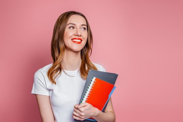 Conceito de educação. menina feliz estudante caucasiana sorrindo desvia o olhar e segurando cadernos, pastas de livros nas mãos isoladas em um fundo rosa no estúdio