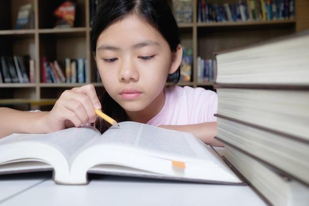 Conceito de educação. menina lendo e escrevendo na biblioteca da escola.